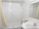 Shower tub, shower curtain, sink and large wall mounted mirror